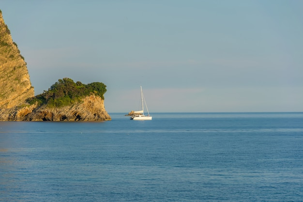 A white yacht sails past the island in the rays of sunset.