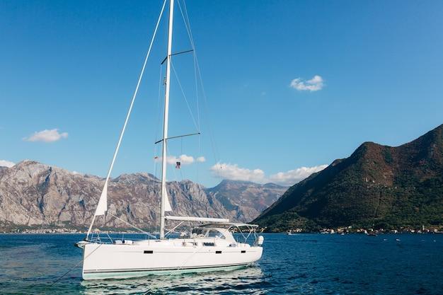 青い空を背景に晴れた日に帆を下げた白いヨット
