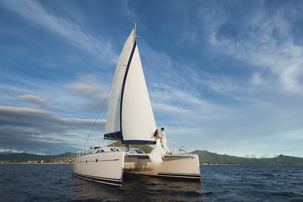 Белая яхта с поднятыми парусами идет по острову в жаркий день.