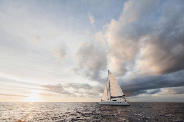 항해 세트가있는 흰색 요트는 더운 날 섬을 따라갑니다.
