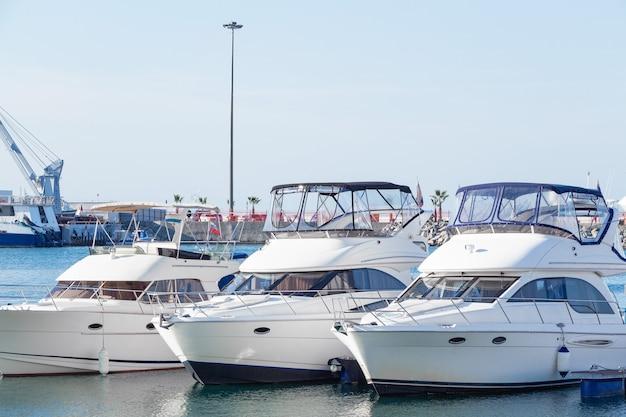 Белые яхты в порту. лодки в гавани голубой воды.
