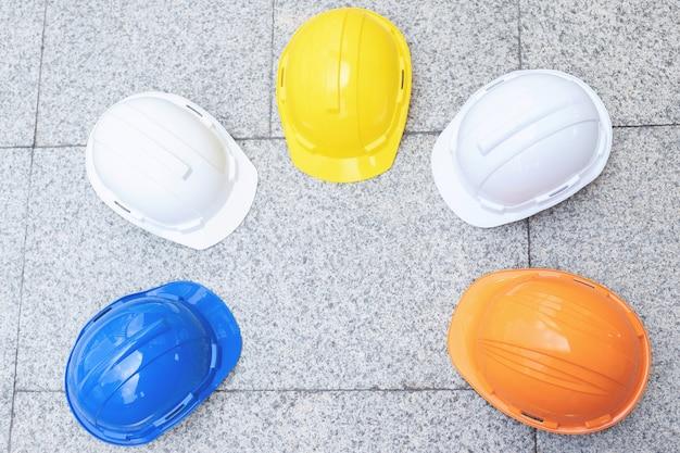 도시의 콘크리트 바닥에 엔지니어 또는 작업자로 노동자의 안전 프로젝트를위한 흰색, 노란색 및 파란색 하드 안전 헬멧 모자