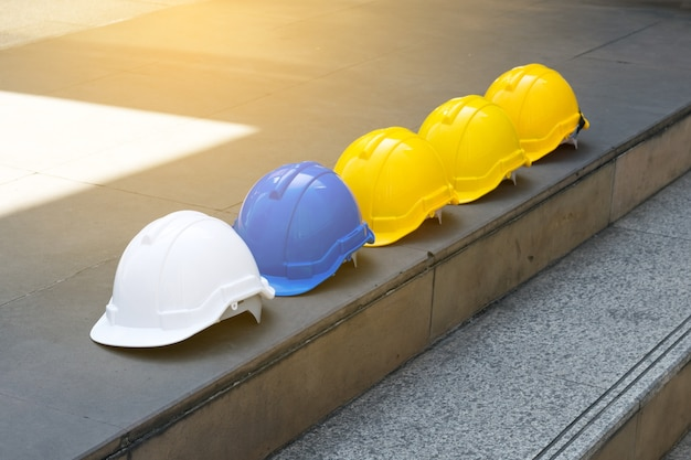 White yellow and blue hard safety helmet hat on concrete floor