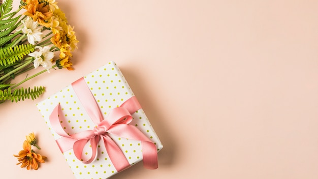 White and yellow flower bouquet near wrapped present box over peach surface