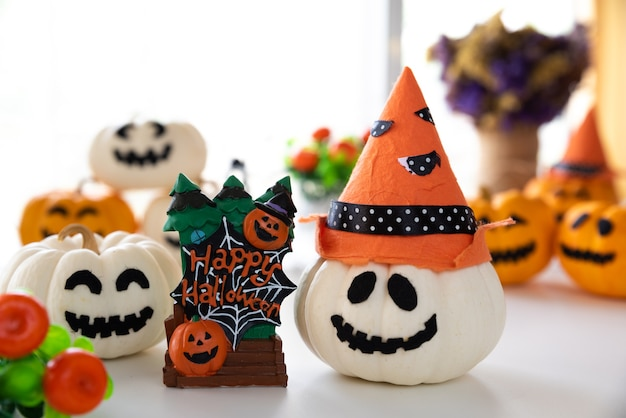 White and yellow ghost pumpkins with witch hat and happy halloween text on board