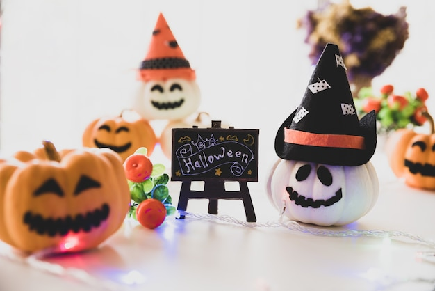 White and yellow ghost pumpkins with witch hat and happy halloween text on borad