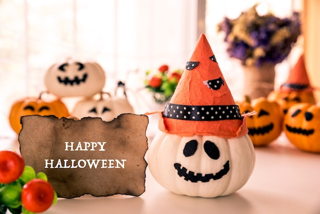White and yellow ghost pumpkins with witch hat and happy halloween text
