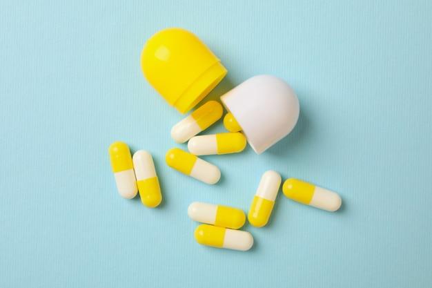 Белые желтые таблетки на синем, крупным планом Premium Фотографии
