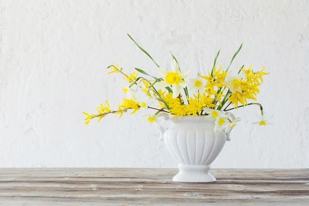 White and yellow spring flowers in vase on surface old white wall