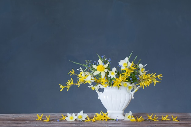 White and yellow spring flowers in vase on wooden table on blue surface