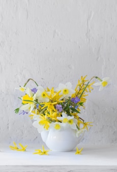 White and yellow spring flowers in vase on wooden table on white surface