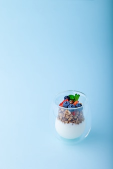 Белый йогурт и мюсли со свежей клубникой, черникой, мятой в стакане