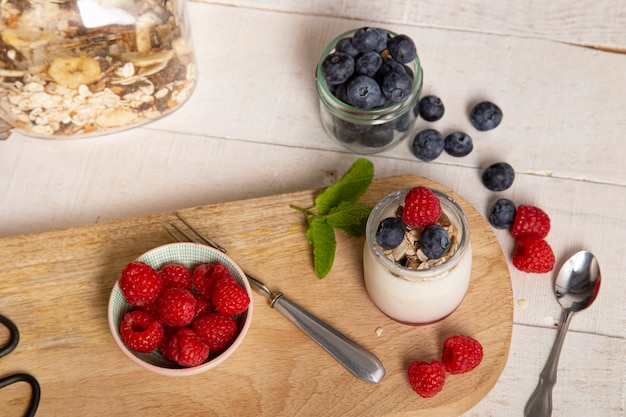 White yogurt glass jar with fresh raspberries and blueberries on serving board on rustic table