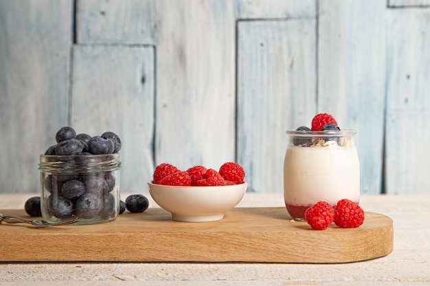 White yogurt with fresh raspberries, blueberries and muesli on a serving board on rustic table on wooden table