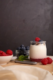 White yogurt with fresh raspberries and blueberries on the serving board on the rustic table