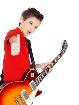 エレクトリックギターを持つ白人の少年は、白で隔離された親指のgeastureを示しています