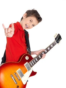 White young boy with electric guitar shows the heavy metal gesture -