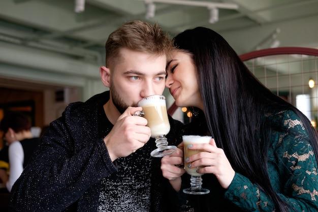 カフェでカプチーノを飲む白い若いカップル
