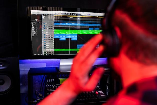 Белый молодой ди-джей записывает новый трек на рабочем месте стереостудии, используя микшер для песен и микрофон.