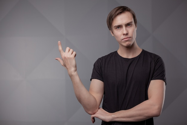 White young man in a black t-shirt and jeans. emotion.