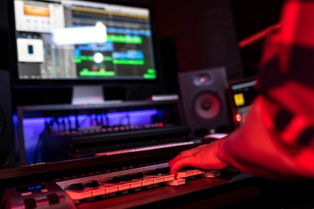 Белый молодой человек записывает новый трек на рабочем месте в стереостудии, используя микшер для песен и клавиатуру.
