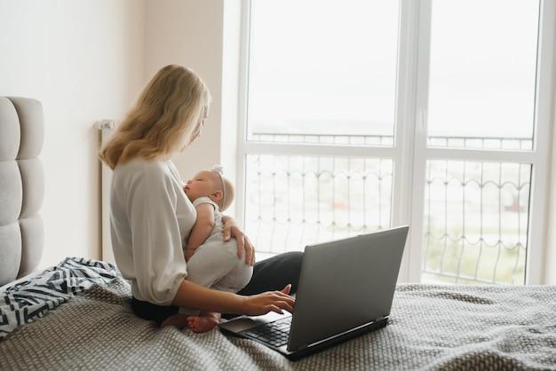 Белая молодая мать сидит с ребенком на кровати и работает на ноутбуке, работает дома