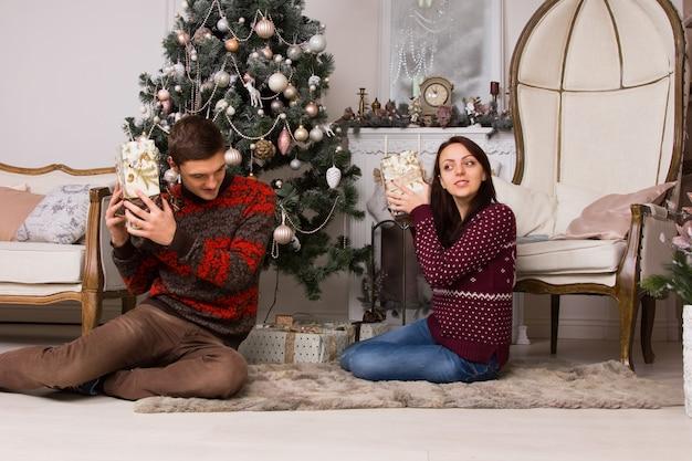 クリスマスツリーと大きなロイヤルチェアの近くでギフトボックスの内容を聞きながら床に座っている白人の若いパートナー。