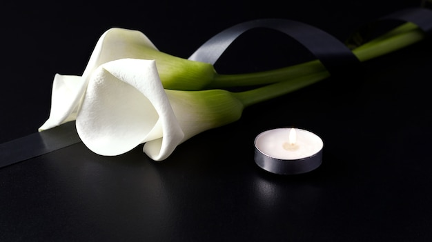 White zantedesia with mourning ribbon and burning candles on black