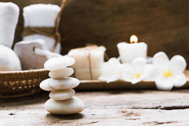 White zen stones and spa and treatment settting with towels, scrub, coconut soap and frangipani flowers on rustic wooden background