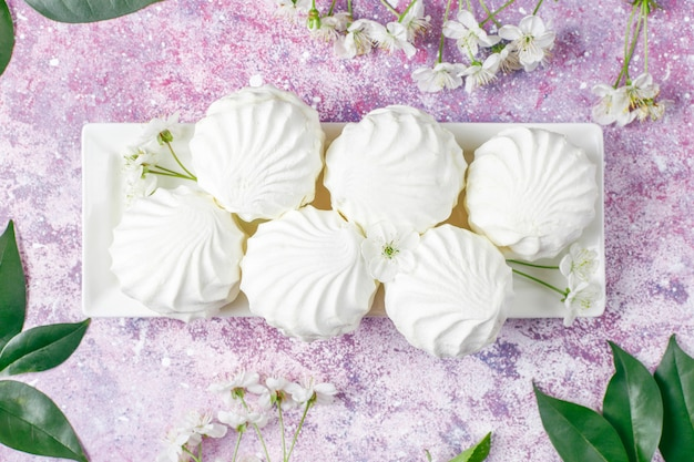White zephyr,delicious marshmallows with spring blossom flowers