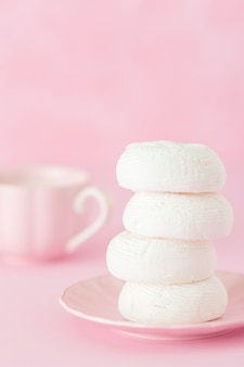Белый зефир dessrt на розовой пластине, чашка кофе с молоком на пастельном розовом фоне.