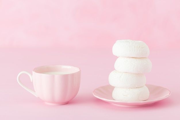 White zephyr dessrt on pink plate, cup of coffee with milk on pastel pink background.