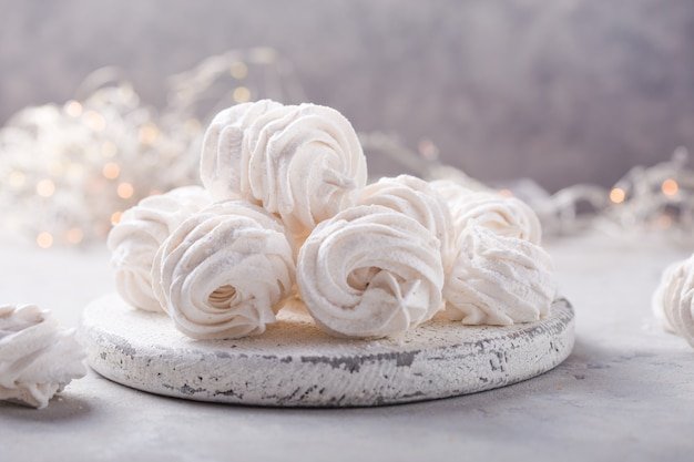 White zephyr on grey concrete surface set of homemade marshmallow meringue, pansy. russian sweetness cuisine