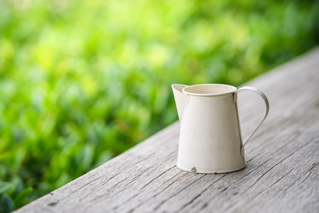 庭の木製のテーブルに白い亜鉛投手