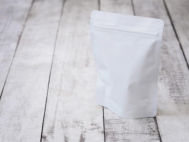Белая сумка на молнии для упаковки пищевых продуктов. пустой пакет zip на винтажном деревянном столе.