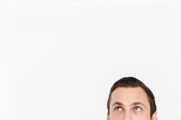 テキストを広告する場所、whitecopyスペースで分離された、上向きに見て緑の目を持つブルネットの男