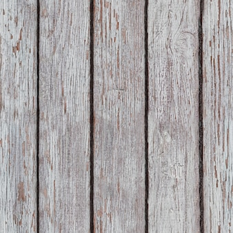 A whitewashed wooden surface worn out due to weather. planks painted white. the texture of the wooden board background