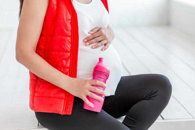 フィットネスwhithの水のボトルの後の若い妊娠中の女性。妊娠中のスポーツ