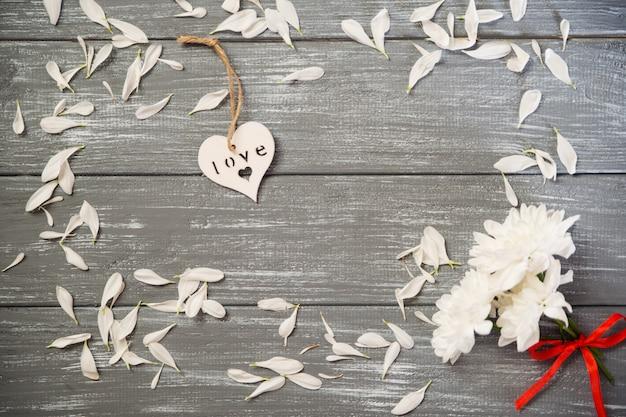 幸せなバレンタインデーの背景。灰色の素朴なwhith花、バレンタインのコンセプトに装飾的な白い木の心。