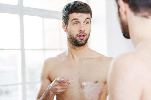 私は誰?鏡に向かって立っている間自分自身を指している欲求不満の若い上半身裸の男