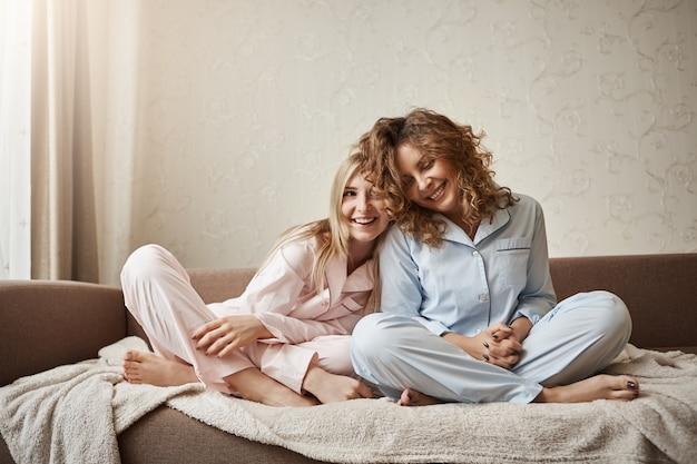誰が母親よりもよく理解できます。ナイトウェアのソファーに座っている2人の美しい女の子、寄り添う、優しい気持ちと愛情を表現する、親しい友人になる、おしゃべりをする、さりげなく話す