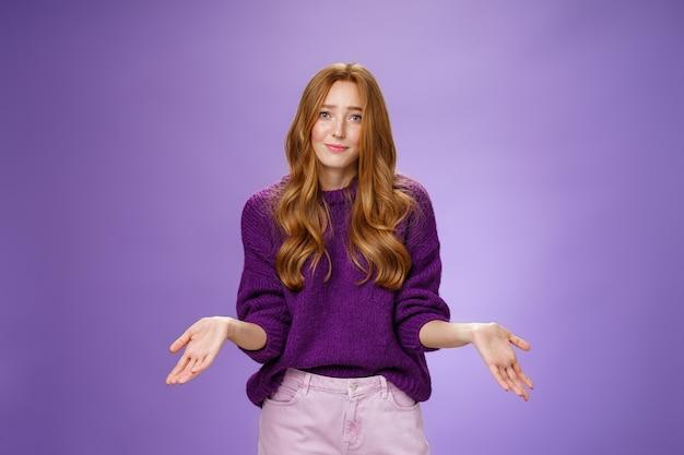 Кого волнует холодок, я не знаю. портрет невежественной и невозмутимой симпатичной рыжей женщины в фиолетовом свитере, ухмыляющейся извиняющимся тоном и пожимающей плечами боком, когда ее спрашивают и озадачивают.