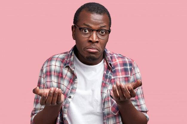 誰も気にしない?躊躇する暗い肌の困惑した男は肩をすくめ、質問に対する答えを知りません、決定をする間は不確かです