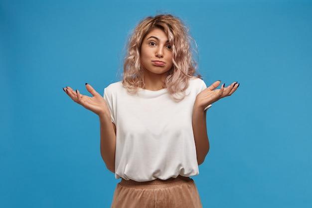 Какая разница, я не знаю, это не моя проблема. портрет стильной молодой европейской девушки в бежевой юбке и белом топе, пожимая плечами