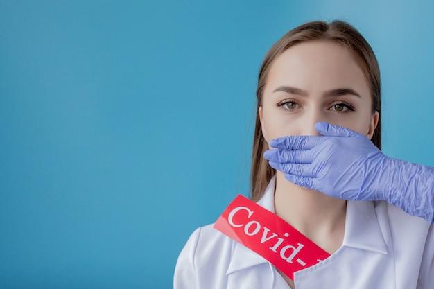 メサージュコロナウイルスと赤い紙を指している医者の女性。世界保健機関whoがコロナウイルス病の新しい公式名covid-19を発表