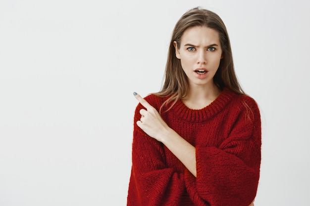 Who invited that drunk guy to party. studio shot of displeased angry young woman in red loose sweater, frowning and arguing with friend, pointing at upper left corner
