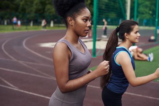 誰が速いですか。リーダーシップと優位性の概念。 2人の若い女性がオープンスタジアムでレースをします