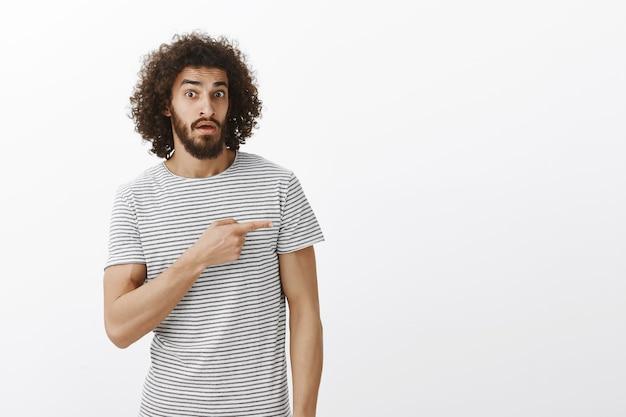 あれは誰。質問された無意識の男がアイテムに興味を示し、人差し指で右を向いており、無知な興味をそそられる表情で凝視している