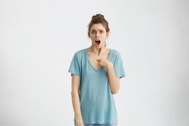 誰、私?質問のような疑わしい表情で見ている憤慨している不幸な腹が立つ若い女性:あなたは私に話しているのですか?本当に?人間の否定的な感情、感情、反応、態度