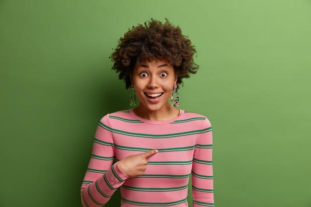 Chi, io? la donna afroamericana sorpresa positiva indica se stessa, non può credere nel suo successo o risultato, guarda con una faccia allegra scioccata, chiede qualcosa, vestita con disinvoltura.
